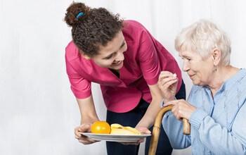 Senior Home Care San Diego Caregiver Serving Meal to Senior
